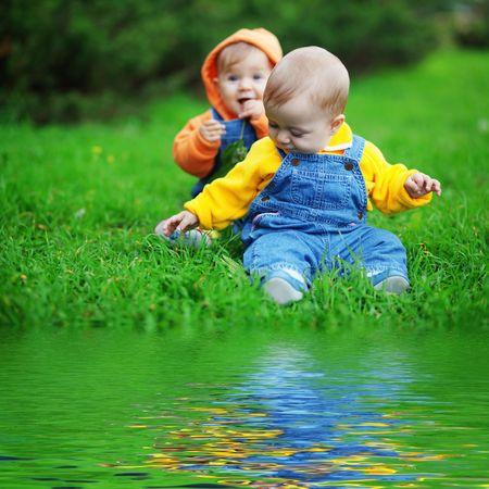 Photo pour Cute twins babies sitting on fresh green grass in park - image libre de droit