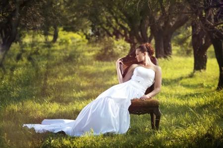 Photo pour Portrait of beautiful bride sitting on the retro char outdoors - image libre de droit