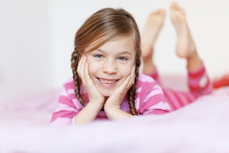 Portrait of a little girl resting on the bed in her bedroom