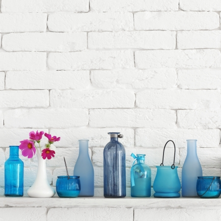 Decorative shelf on white brick wall with blue bottles on it