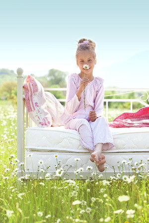 Photo pour 7 years old child resting on comfortable bed in spring field - image libre de droit