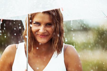 Portrait of beautiful young girl walking with umbrella under rain
