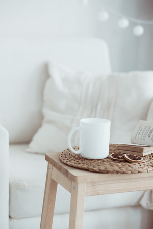Still life interior details, cup of coffee and a book near white cozy chair
