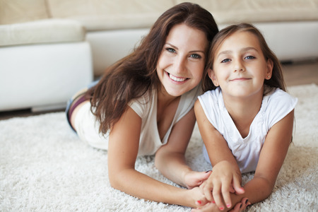 Mother with her preteen daughter having fun on a white carpet in living room at homeの写真素材