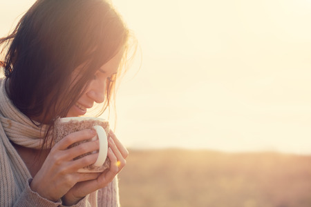 Photo for Woman wearing warm knit clothes drinking cup of hot tea or coffee outdoors in sunlight - Royalty Free Image
