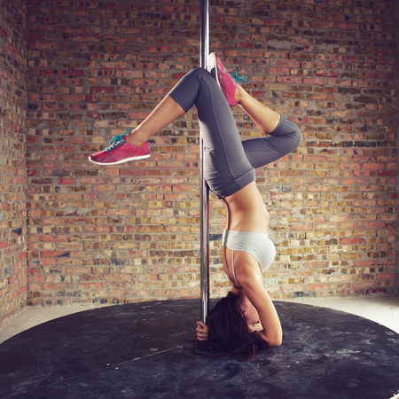 Young pole dancer woman wearing grey sports wear and colorful sneakers trains on grunge interior with brick walls, square composition