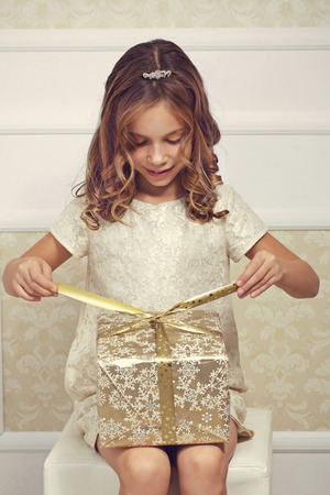 Portrait of luxury little princess with gold gift boxの写真素材