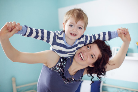 Photo pour Young mother playing with her 2 years old little son at the bedroom - image libre de droit