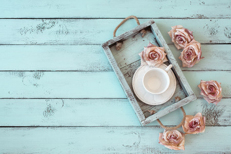 Vintage wooden tray with porcelain teacup and rose buds on shabby chic mint background, top view point