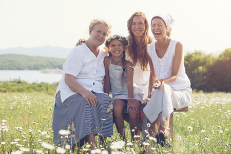 Foto de Four generations of beautiful women sitting together in a camomile field and smiling - Imagen libre de derechos