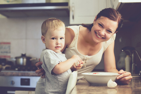 Photo pour Mom with her 2 years old child cooking holiday pie in the kitchen to Mothers day, casual lifestyle photo series in real life interior - image libre de droit