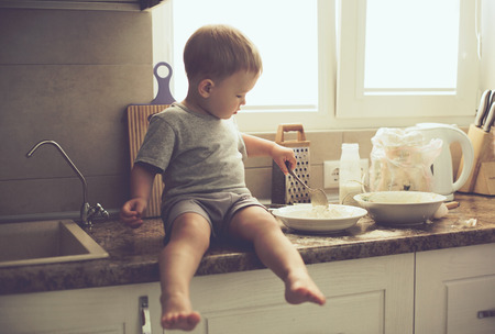 Photo for 2 years old child cooking alone in the kitchen, casual lifestyle photo series in real life interior - Royalty Free Image