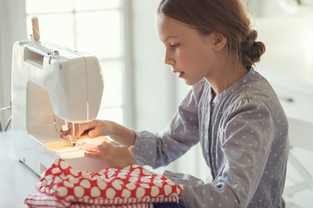 9 years old child studying work with sewing machine