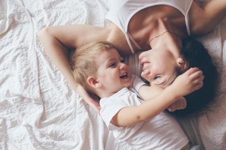 Photo pour Young mother with her 2 years old little son dressed in pajamas are relaxing and playing in the bed at the weekend together, lazy morning, warm and cozy scene. Pastel colors, selective focus, top view. - image libre de droit