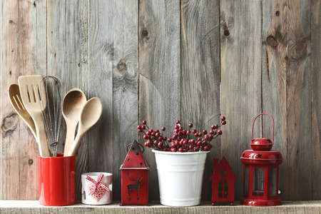 Kitchen cooking utensils in ceramic storage pot and Christmas decor on a shelf on a rustic wooden wall