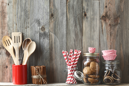 Photo pour Kitchen cooking utensils in ceramic storage pot and cookies on a shelf on a rustic wooden wall - image libre de droit