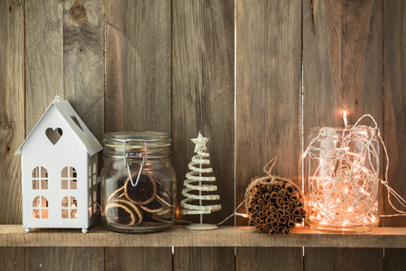 Foto de Sweet home. White Christmas decor on vintage natural wooden background. Cinnamon sticks and dried citrus. Cafe shelf. - Imagen libre de derechos
