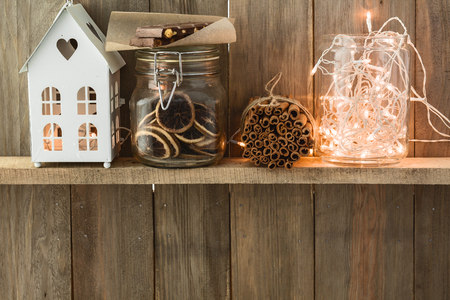 Sweet home. White Christmas decor on vintage natural wooden background. Cinnamon sticks and dried citrus. Cafe shelf. Space for custom text.