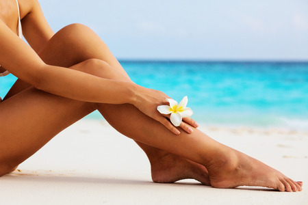 Foto per Women's beautiful sexy legs on the beach - Immagine Royalty Free