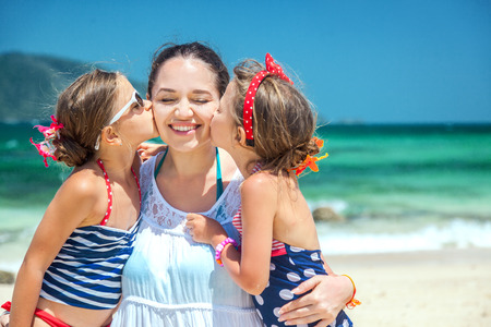 Photo for Mom with her two children having fun at the tropical beach, daughters kissing mother - Royalty Free Image