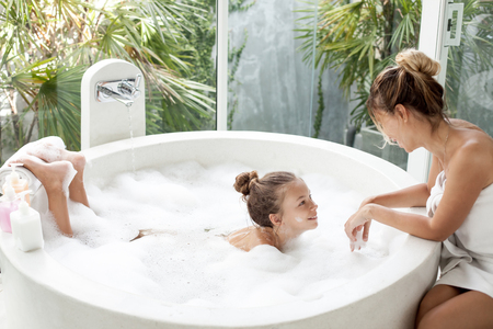 Photo pour Mom washing her child in luxury hotel outdoor bath with a foam, still life - image libre de droit