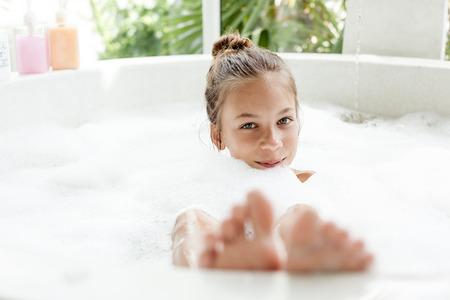 Kid girl washing with a foam in luxury hotel outdoor bath, still life