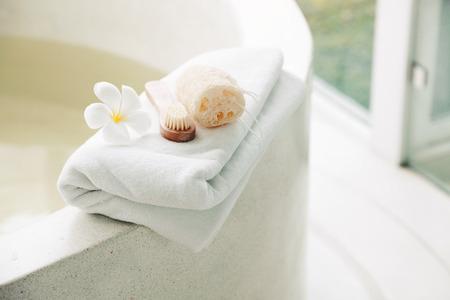 Foto de Spa decoration, natural organic products on a bathtube. Loofah, towel and frangipani flower. - Imagen libre de derechos