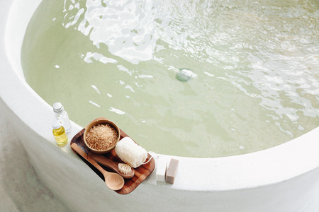 Spa decoration, natural organic products on a bathtube. Loofah, towel and frangipani flower, top view