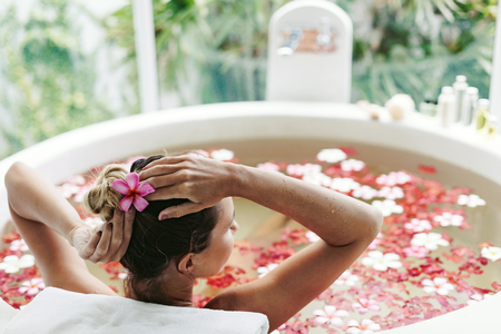 Photo pour Woman relaxing in round outdoor bath with tropical flowers, organic skin care, luxury spa hotel, lifestyle photo - image libre de droit