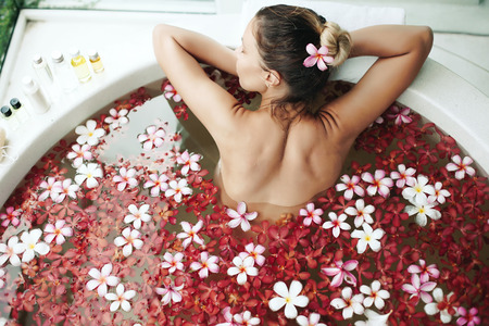 Photo pour Woman relaxing in round outdoor bath with tropical flowers, organic skin care, luxury spa hotel, lifestyle photo, top view - image libre de droit