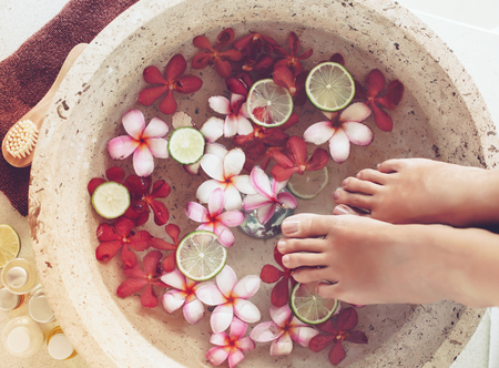 Photo pour Foot bath in bowl with lime and tropical flowers, spa pedicure treatment, top view - image libre de droit