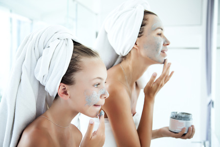 Photo for Mother and tween daughter make a clay facial mask, family scin care in the bathroom - Royalty Free Image