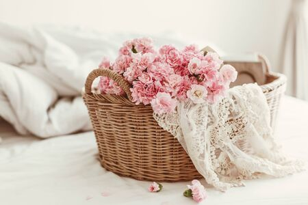 Photo pour Shabby chic style. Pink pastel flowers in wicker basket on the bed. - image libre de droit