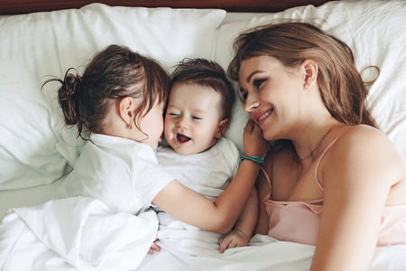 Foto de Young mom with her 5 years old dauhter and 4 months old baby dressed in pajamas are relaxing and playing in the bed at the weekend together, lazy morning - Imagen libre de derechos