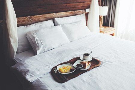 Photo for Brekfast on a tray in bed in hotel, white linen, wooden intreior - Royalty Free Image