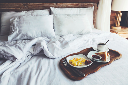Foto de Brekfast on a tray in bed in hotel, white linen, wooden intreior - Imagen libre de derechos