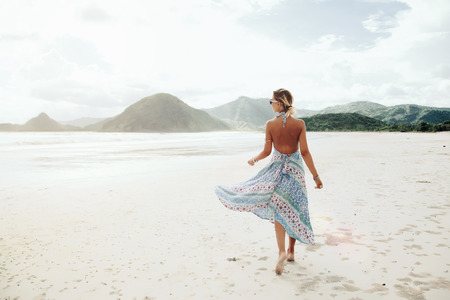 Photo pour Woman wearing ethnic flying dress walking barefoot at the beach, Lombok, Indonesia - image libre de droit
