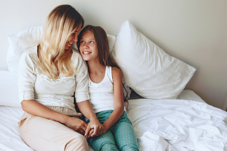 Photo for Mom with her tween daughter relaxing in bed, positive feelings, good relations. - Royalty Free Image