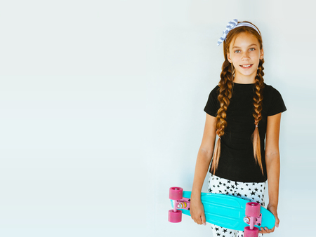 Photo for Pre teen girl wearing cool fashion clothing posing with colorful skateboard against white wall - Royalty Free Image