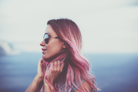 Photo for Woman with pink hair standing on the mountain top over blue sea view, photo toned - Royalty Free Image