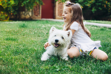 Photo pour Child playing with English Highland White Terrier dog on grass in the backyard - image libre de droit