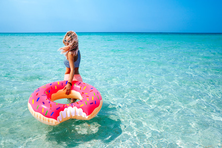 Photo pour Woman swimming with inflatable donut on the beach in summer sunny day - image libre de droit