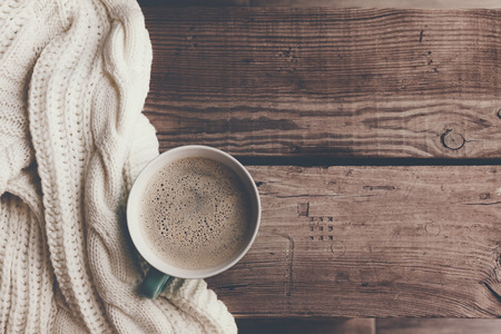 Photo pour Cup of hot coffee on rustic wooden table, closeup photo warm sweater with mug, winter morning concept, top view - image libre de droit