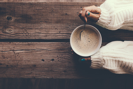 Woman holding cup of hot coffee on rustic wooden table, closeup photo of hands in warm sweater with mug, winter morning concept, top view