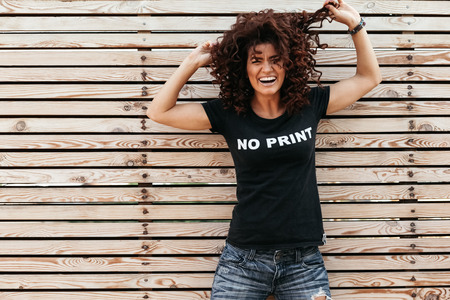 Photo pour Hipster girl with curly hair wearing t-shirt and jeans posing against wooden wall, swag street style - image libre de droit