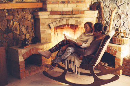 Photo pour Mom with child reading book and relaxing by the fire place some cold evening, winter weekends, cozy scene - image libre de droit