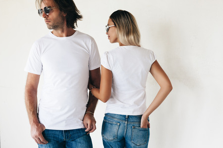 Two hipster models man and woman wearing blanc t-shirt, jeans and sunglasses posing against white wall, toned photo, front and back tshirt mockup for couple