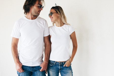 Photo for Two hipster models man and woman wearing blanc t-shirt, jeans and sunglasses posing against white wall, toned photo, front tshirt mockup for couple - Royalty Free Image