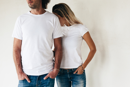 Photo pour Two models man and woman wearing blanc t-shirt posing against white wall, toned photo, front tshirt mockup for couple - image libre de droit