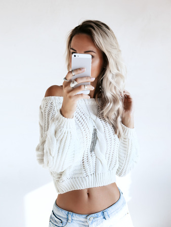Photo for Blond girl wearing white sweater and jeans shorts making selfie by her smartphone in the mirror. Blogger taking photo of self fashion look. - Royalty Free Image
